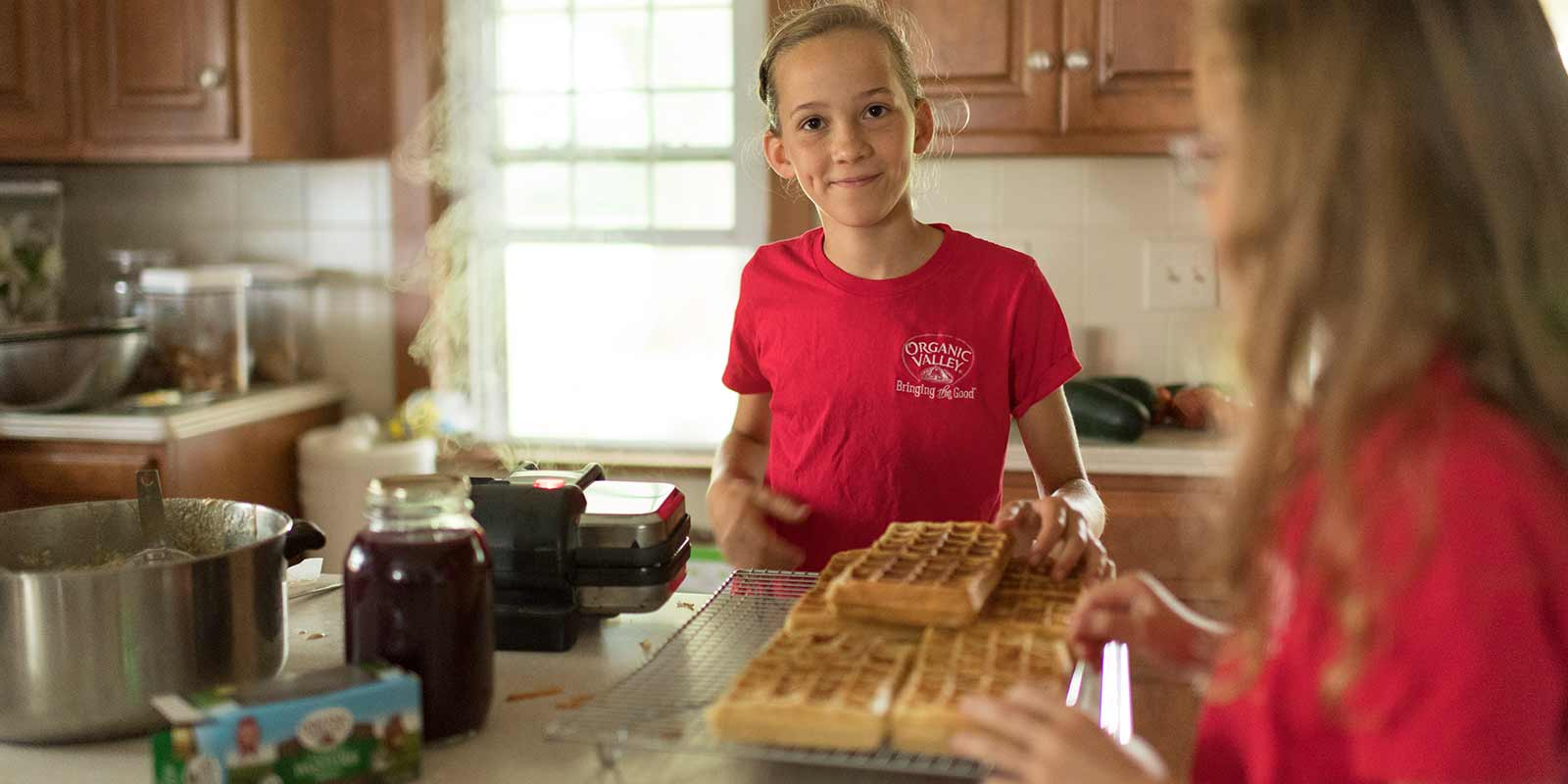 A girl wearing a red shirt smiles at the camera while standing in front of a pile of freshly made waffles in her family's kitchen