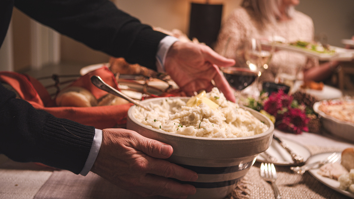 A man places a large bowl of mashed potatoes topped with butter on a Thanksgiving table surrounded by people.