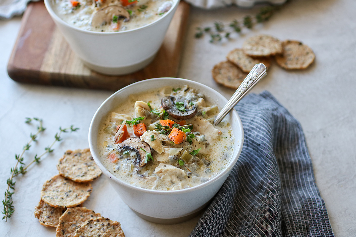 A hearty chicken and wild rice soup loaded with chicken, carrots, and mushrooms, topped with a sprinkle of pepper.