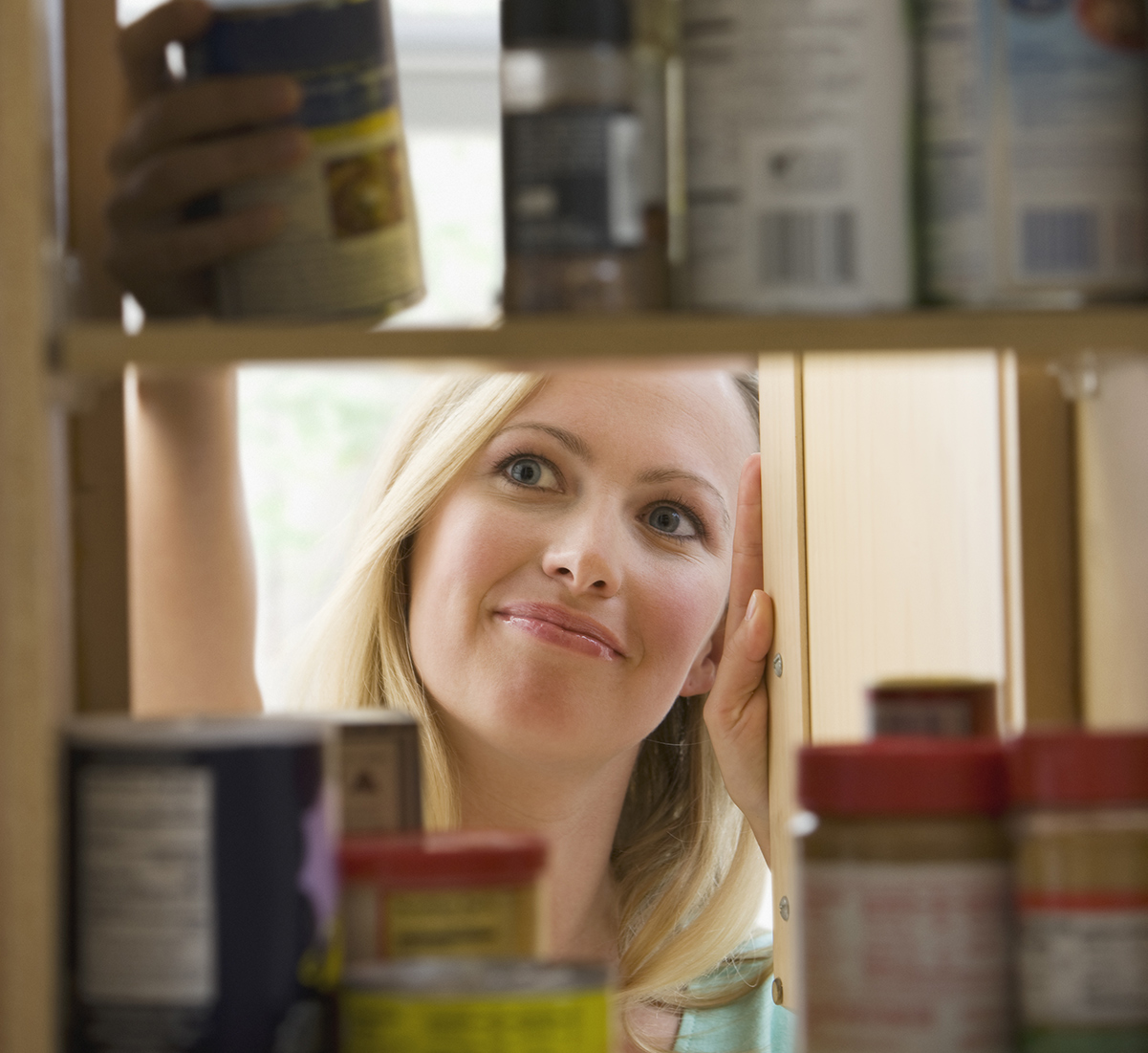 Women looks into kitchen cabinet and grabs a can of vegetables.
