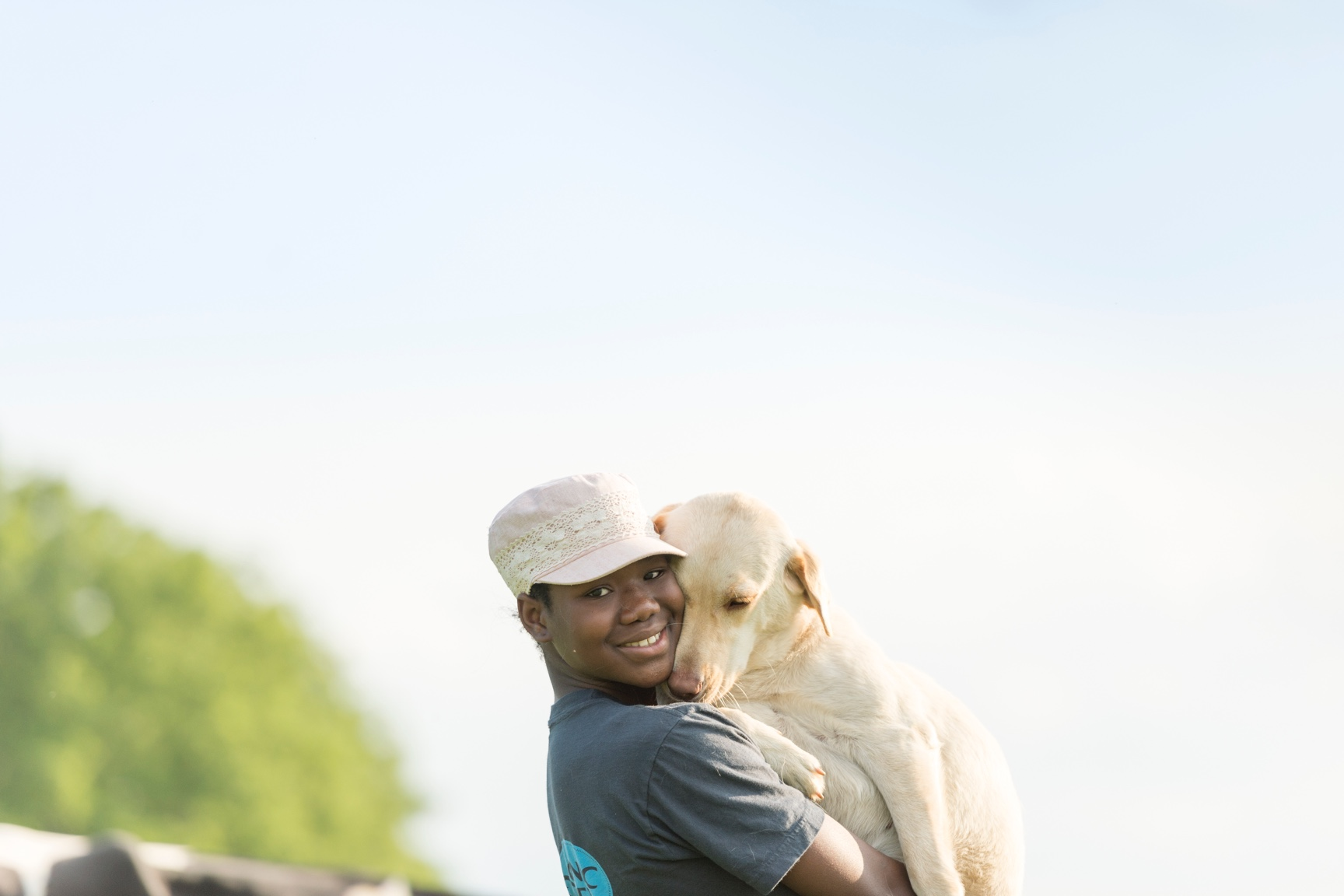 A woman smiles at the camera while holding her yellow lab, which lovingly snuggles into her neck.