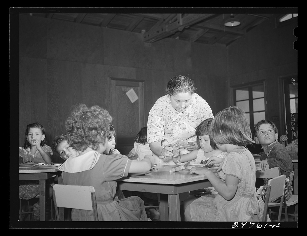 A black and white photo of children in old fashioned clothing sitting at tables being served food by a woman. (Source: Library of Congress)
