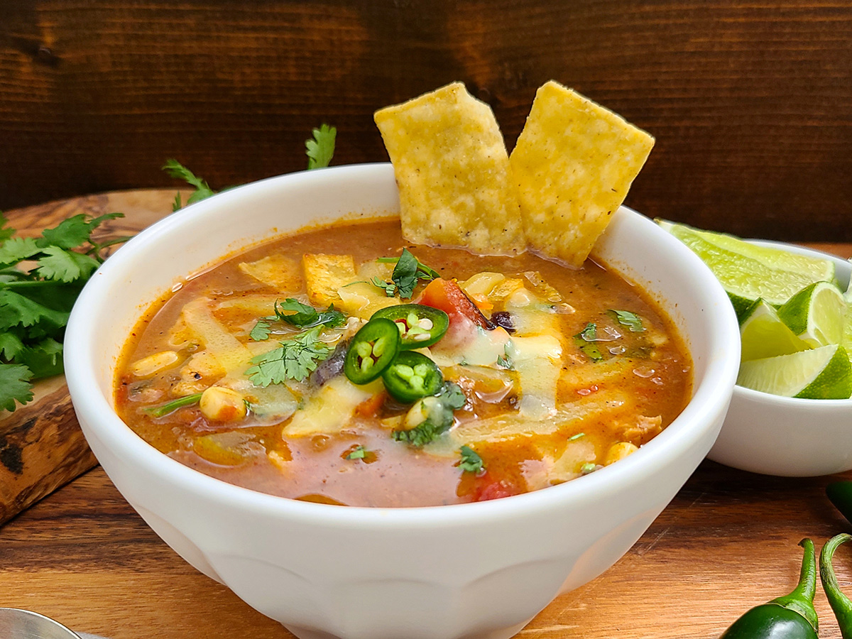 A colorful tomato-based chicken tortilla soup topped with corn chips, shredded cheese, cilantro leaves, and sliced jalapeños.