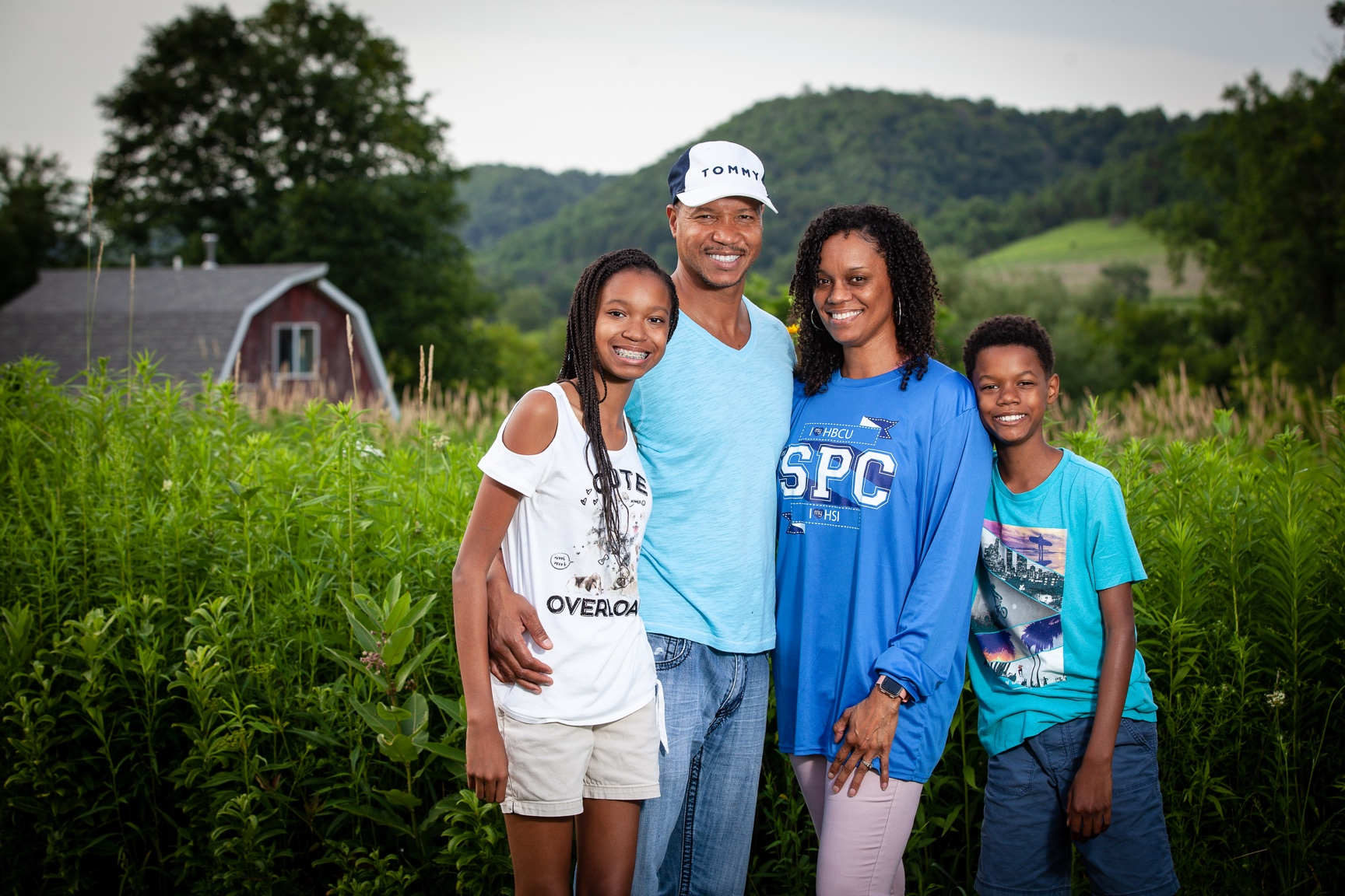 A father, mother, daughter and son pose in front of tall grass and a red barn in the hills of Wisconsin.