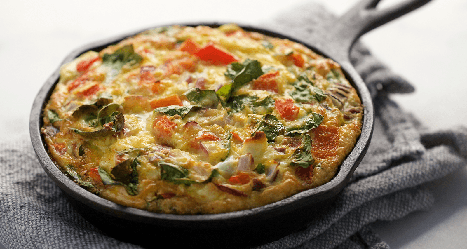 Organic Mama Veggie Frittata baked in a cast iron pan.