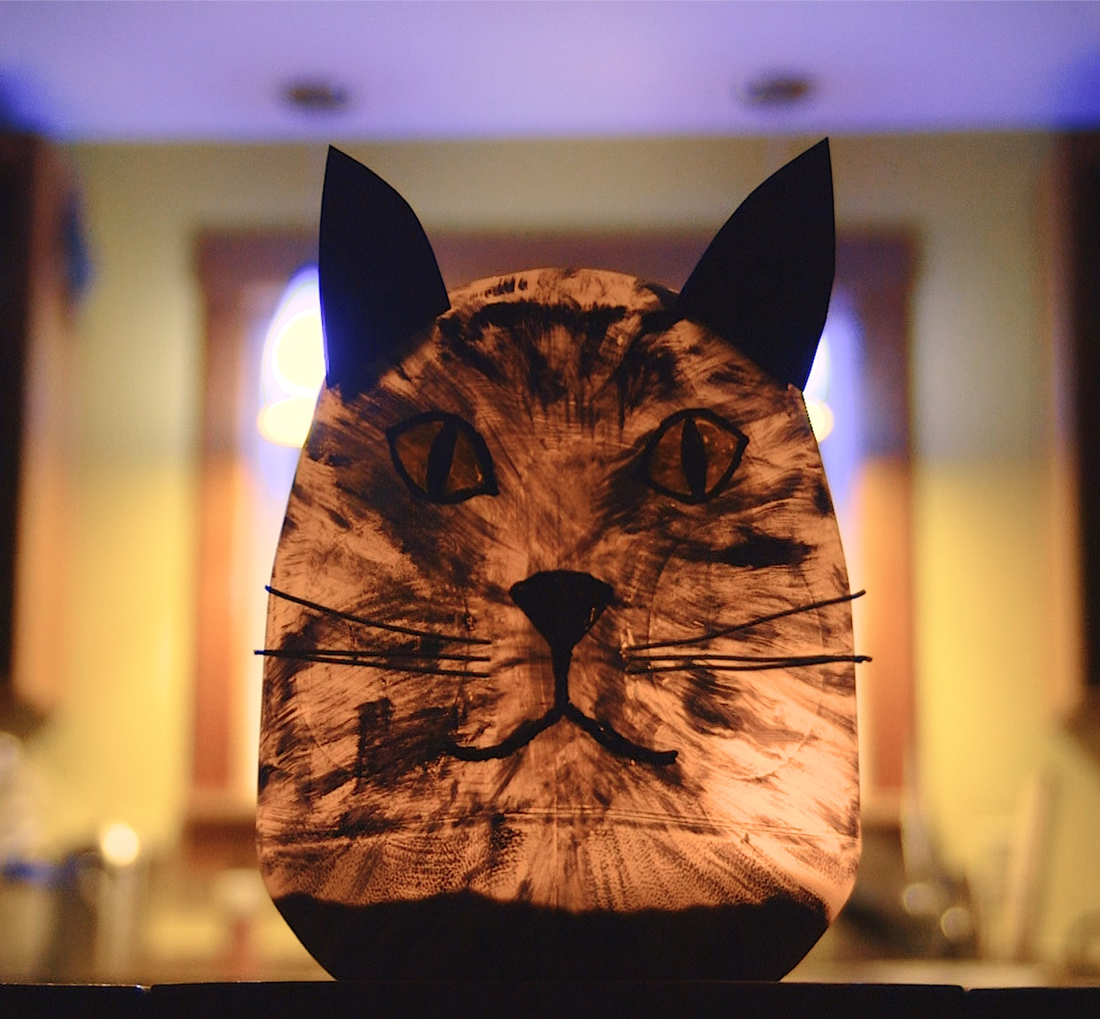 A completed and illuminated milk jug luminary with a cat face and ears.