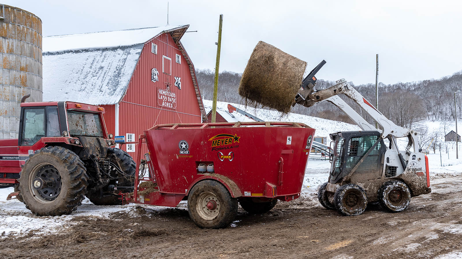 Using the end-loader to lift a round hay bale into a trailer pulled by a tractor.