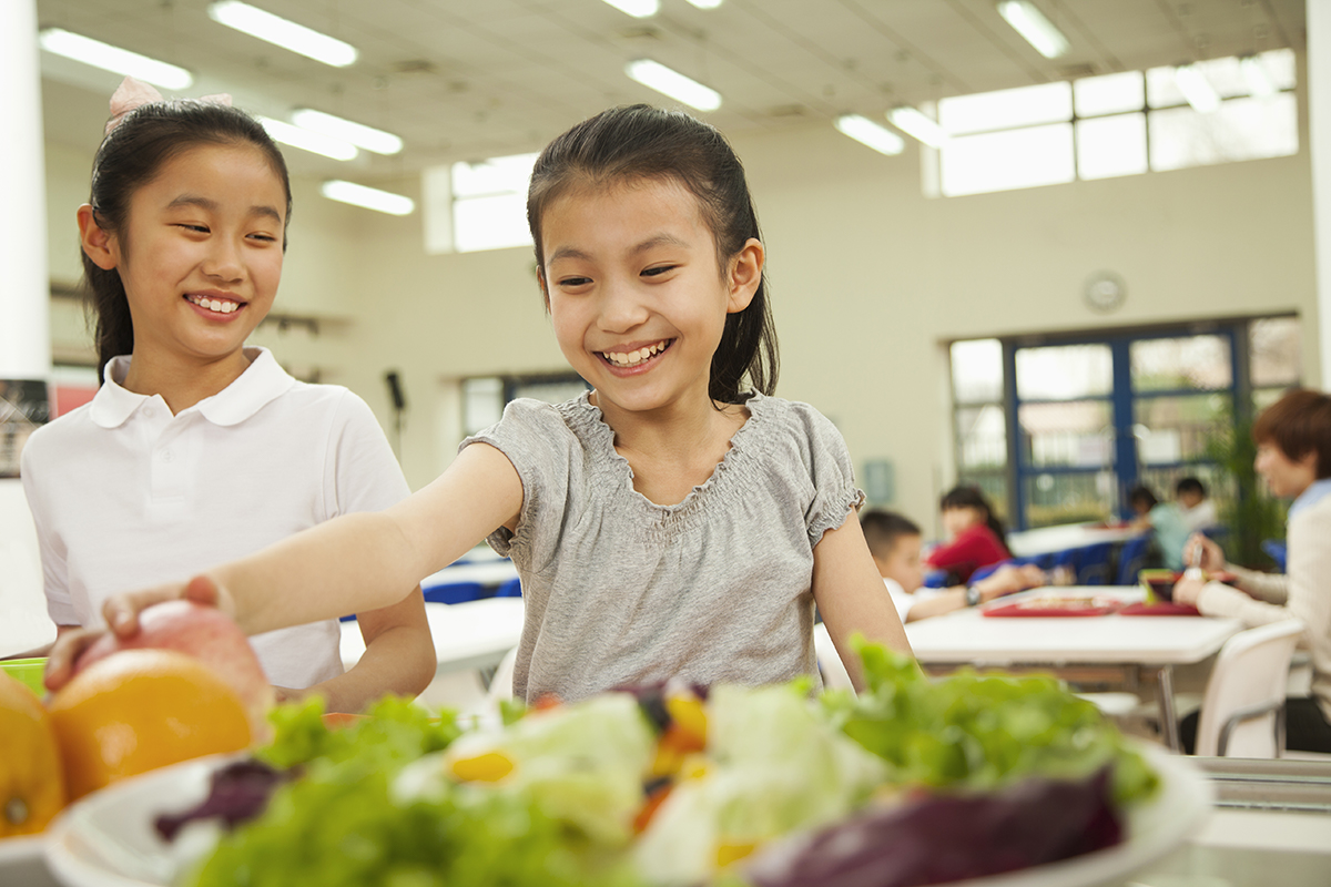 Two young girls smile while taking fresh foods from their school lunch salad bar.