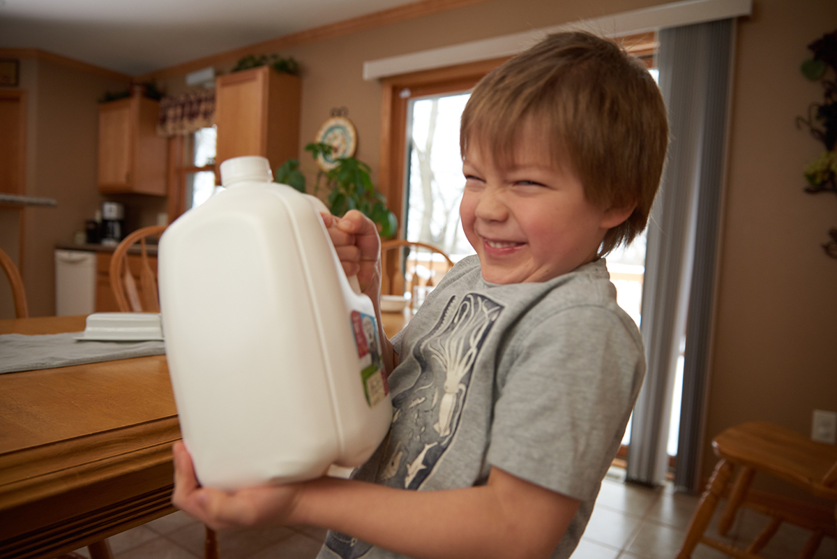 Young boy holds a gallon of Organic Valley milk and smiles to the camera.