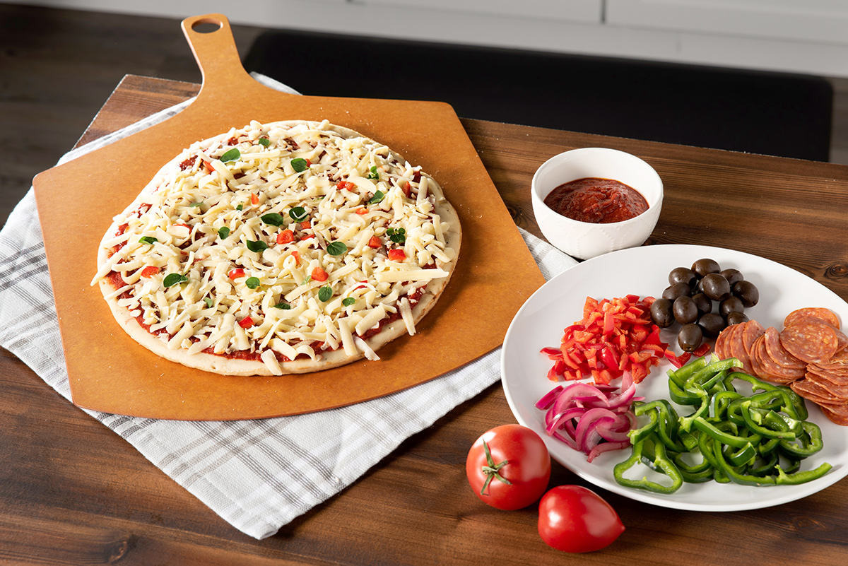 An unbaked pizza sits on a pizza peel with a plate of toppings sitting next to it.
