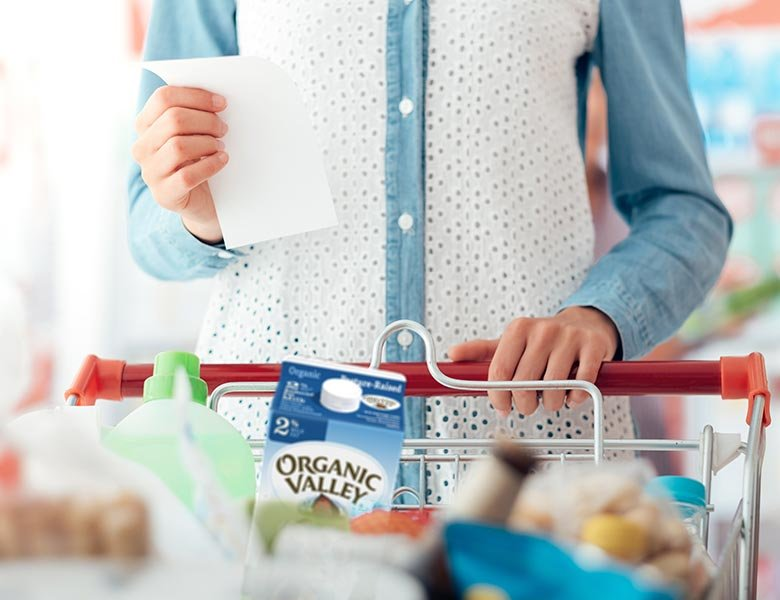 Person shopping with Organic Valley milk in their cart