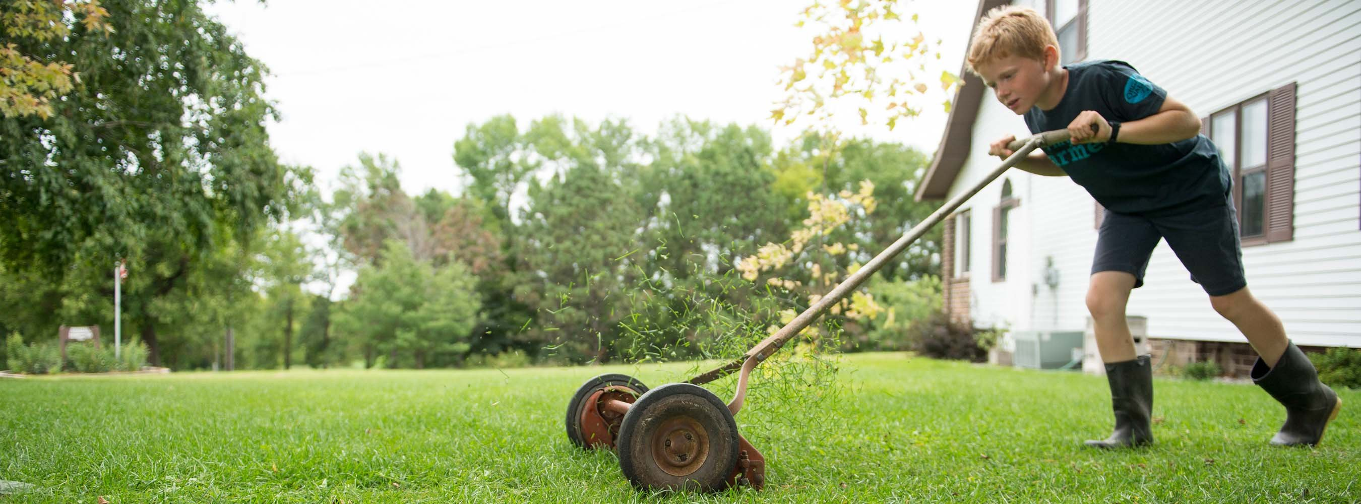 A young boy on the Elsenpeter family farm mowing the lawn