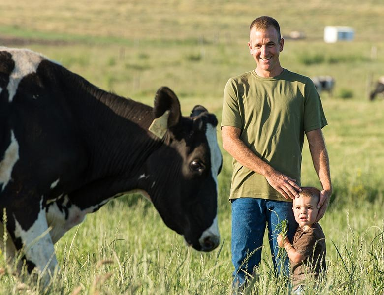 A man and a his son standing next to a cow in a field.